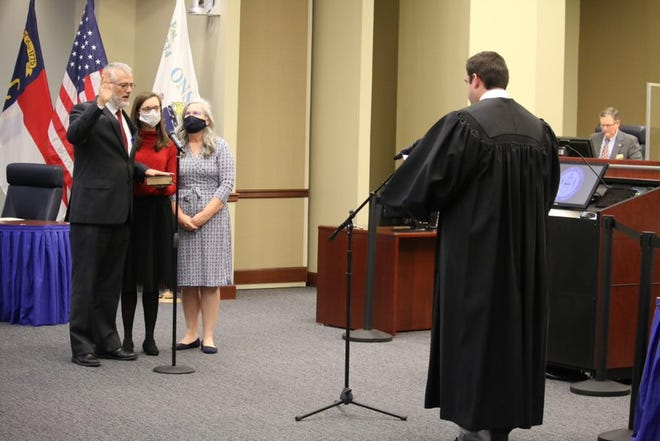 Onslow County Board of Commissioner Mark Price, left, is sworn into office by District Court Judge William Shanahan at the Jan. 4 meeting. Price is filling Shanahan's unexpired term on the county board after his election as judge.