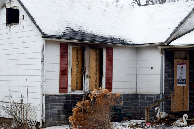 Boards cover broken windows following a fire at a house on Pottawatomie Street.