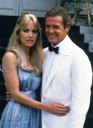 "Actor Roger Moore, right, poses with his co-star Tanya Roberts from the James Bond film ""A View to a Kill,"" in Chantilly, France on Aug. 17, 1984. [AP Photo/Alexis Duclos, File]"