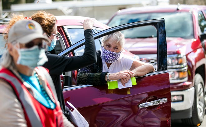 Jacque Hall leans in the window of her SUV while talking with RN Marica Grayson after getting vaccinated with the COVID-19 Moderna vaccine Tuesday afternoon in the parking lot of the Marion County Health Department.