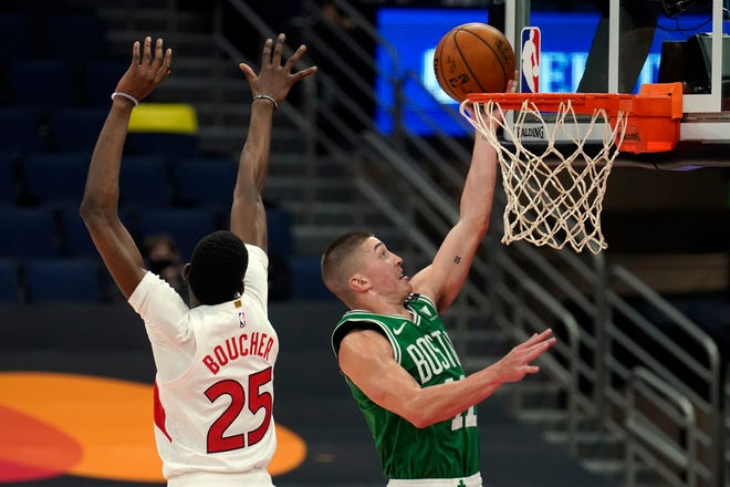 Boston Celtics guard Payton Pritchard drives past Toronto's Chris Boucher (25) for two of his 23 points during the second half of Monday's game in Tampa, Fla. Pritchard and Boucher were college teammates at Oregon.
