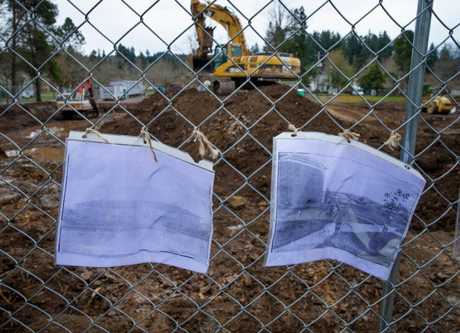 Faded photographs of the old school hang on a fence as crews prepare the ground for new construction on the site of the old Edison Elementary School in Eugene. The old building was torn down to make way for a new school to be completed in the fall of 2022.