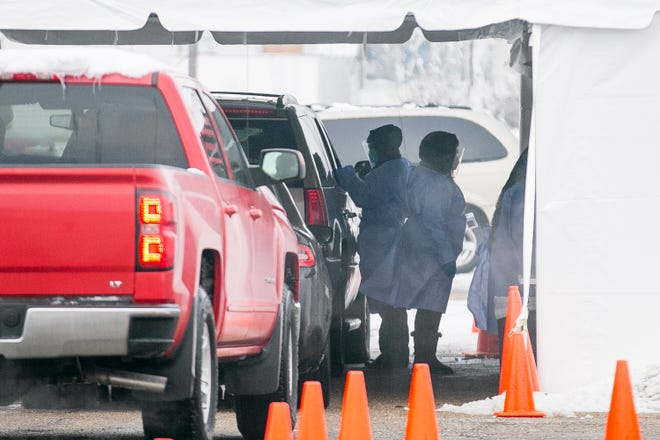 COVID-19 tests are administered at a drive-thru site on Jan. 5 at the former Kmart on Sandy Hollow Road in Rockford. The state's seven-day positive COVID-19 test rate on Tuesday dropped to its lowest point since Oct. 23.