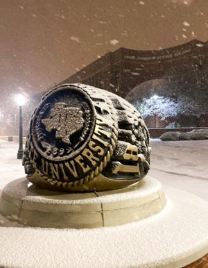 Snowflakes fall on and around the Tarleton State University Ring statue on campus during a winter storm that moved through the area on New Year's Eve.