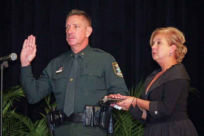 Sarasota County Sheriff Kurt Hoffman rests his left hand on a Bible held by his wife Teri Hoffman, as he recites the oath of office as administered  by 12th Circuit Chief Judge Kimberly Bonner, Tuesday afternoon at the Venice Community Center.