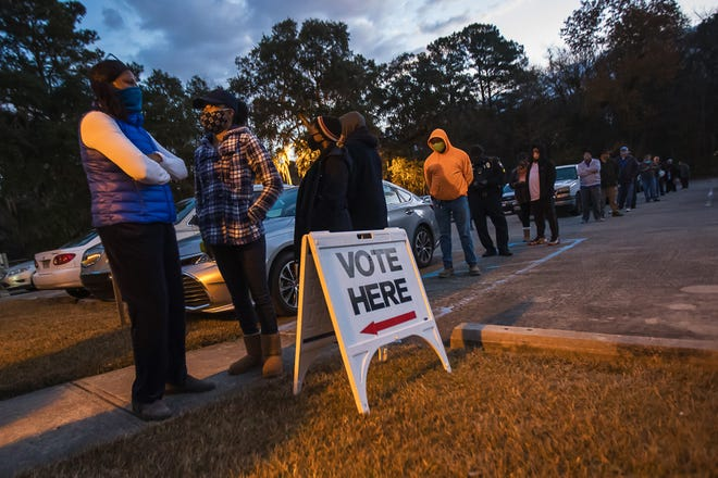 Voters stand in line during the early morning hours before the polls open at the Progressive Recreation Center on Ogeechee Road during the senate runoff election on Tuesday.