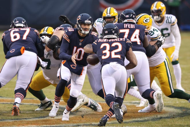 Chicago Bears linemen clear a gap for running back David Montgomery (32) on Sunday, Jan. 3, 2021, in Chicago.