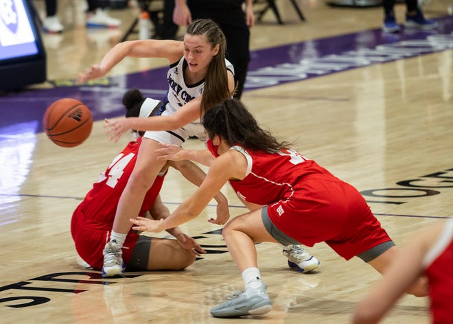 Holy Cross guard Cara McCormack works to grab a loose ball between two Boston University defenders during Tuesday's game.