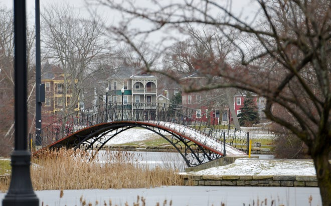 WORCESTER - The iron bridge in Elm Park spans the ice-covered lagoon in snowy, gray weather on Tuesday.