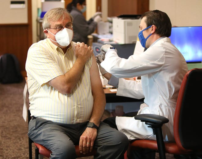University of Florida President Kent Fuchs gets his first dose of the Pfizer/BioNtech COVID-19 vaccine from Dr. Clayton Johnson, the assistant director of pharmacy services at UF Health, during a press conference and inoculation session for UF faculty over the age of 65 on Tuesday, at the UF Health Cancer Center in Gainesville. [Brad McClenny/The Gainesville Sun]