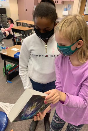Third-grade students at Norton Elementary School in Gainesville look at one of the dictionaries donated by the Rotary Clubs of Alachua County.