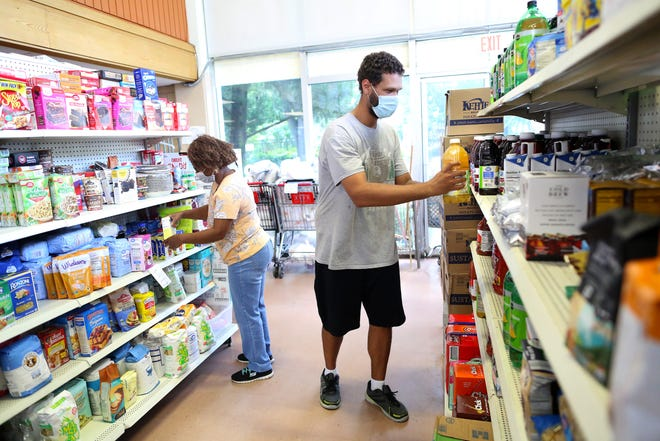 Brennan Lewis, right, and Irene Williams, who work at Bread of the Mighty Food Bank, organize food items on the shelves at the Gainesville food bank on Sept. 9.