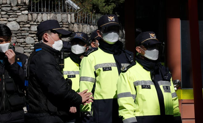 South Korean police officers stand outside a residence of former President Lee Myung-bak in Seoul, South Korea, on Nov. 2, 2020. Lee was sent back to prison after the country's top court upheld a 17-year prison term on him over corruption crimes.