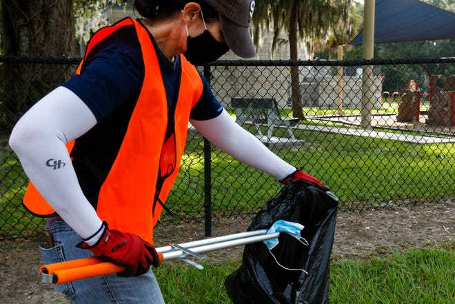A volunteer picks up a mask along Southwest Third Street during the 29th Annual Great American Cleanup hosted by Keep Alachua County Beautiful on Sept. 26.