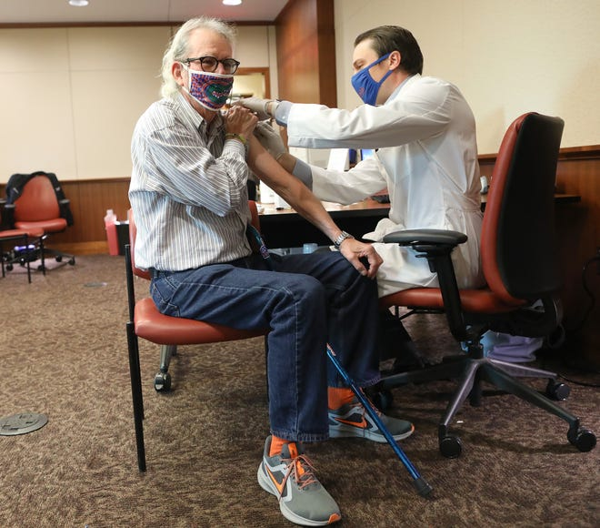 UF journalism lecturer Mike Foley, 74, gets the first dose of the Pfizer/BioNtech COVID-19 vaccine from Dr. Clayton Johnson, assistant director of pharmacy services at UF Health, during a press conference and inoculation session for UF faculty over the age of 65 on Tuesday.