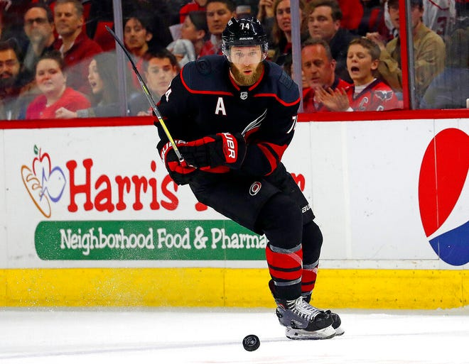 """FILE - In this Jan. 3, 2020, file photo, Carolina Hurricanes' Jaccob Slavin (74) retrieves the puck against the Washington Capitals during the third period of an NHL hockey game in Raleigh, N.C. Slavin has been a part of two straight playoff trips for the Hurricanes and said the number of returning players could be """"a big advantage"""" as they work through a shortened training camp. (AP Photo/Karl B DeBlaker, File)"""
