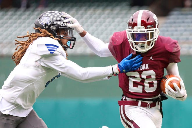 Red Oak running back Iverson Young (28) gives a stiff-arm to Mansfield Summit defensive back Sean Smith (5) during the first half of their Class 5A Division I state quarterfinal game on New Year's Day afternoon at Globe Life Park in Arlington. The Hawks' season ended with a 41-38 loss to the Jaguars.