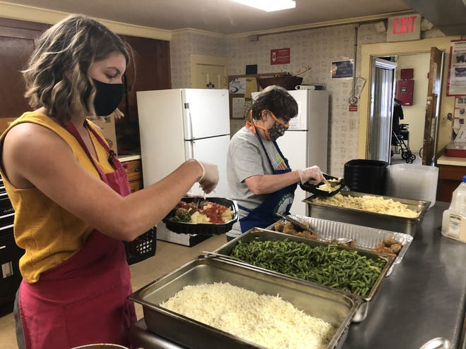 Our Neighbors' Table has been battling hunger for years, and the pandemic has made that effort more crucial than ever. Shown here, volunteers Shannon Bullen, left, and Meader Joan, right, prepare meals for families in need.