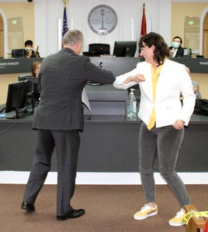 Councilwoman Trisha Butler and Mayor Joe Pitts share a COVID elbow bump after she is sworn into office.