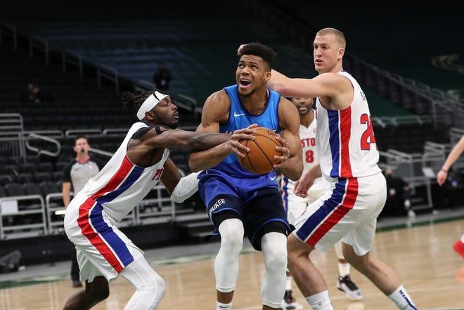 Bucks forward Giannis Antetokounmpo drives against Pistons forward Jerami Grant, left, and center Mason Plumlee during the Pistons' 125-115 loss on Monday, Jan. 4, 2021, in Milwaukee.