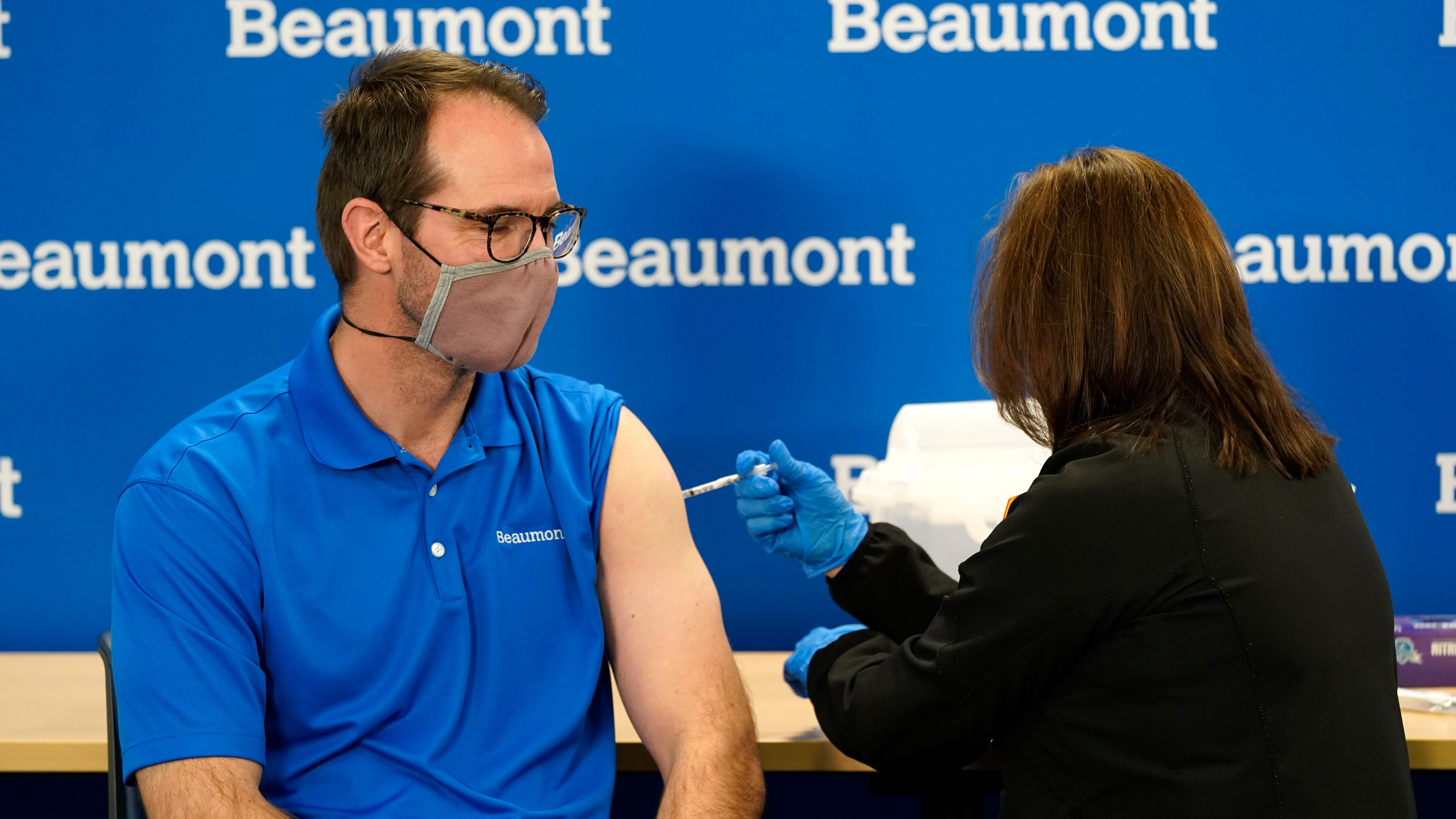 Dr. Nick Gilpin receives his second Pfizer-BioNTech COVID-19 vaccine shot from registered nurse Susan Grant at Beaumont Health in Southfield on Tuesday.