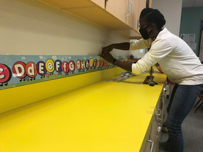 Shatreetia Cordell, who is a Head Start curriculum specialist for the district, lines up an alphabet poster along the counter top of a classroom at James Stephens Pre-K Center in Fort Myers.