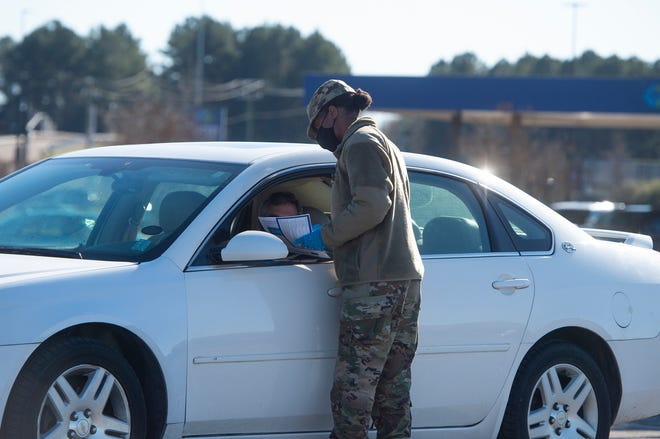 A Mississippi National Guardsmen checks in a person at the staging area at the Rankin County free drive-thru COVID-19 vaccination clinic at the Trustmark Park parking lot in Pearl, Miss., on Jan. 5.