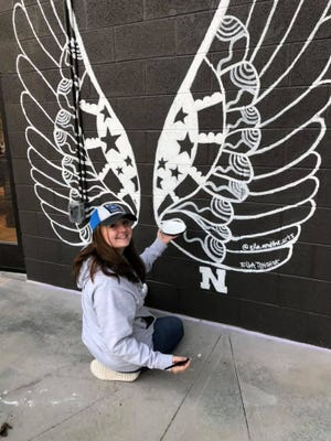 Ella Pinchok, 15, draws an impressive pair of wings on an exterior wall at 35 North-Farragut Wednesday, Dec. 9, 2020.
