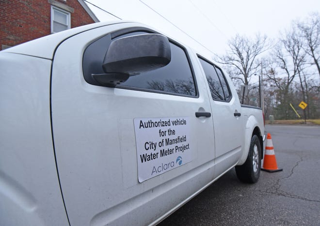An authorized City of Mansfield Water Meter Project truck marks the location of another new meter in Mansfield on Tuesday afternoon.