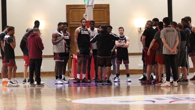 The New Mexico State men's basketball team talks things over during a practice at Arizona Grand Resort & Spa in Phoenix, Arizona.