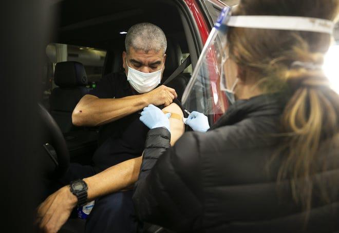 El Jefe de Bomberos de Phoenix, Tony Benites, recibe la vacuna Pfizer-BioNTech contra el COVID-19.