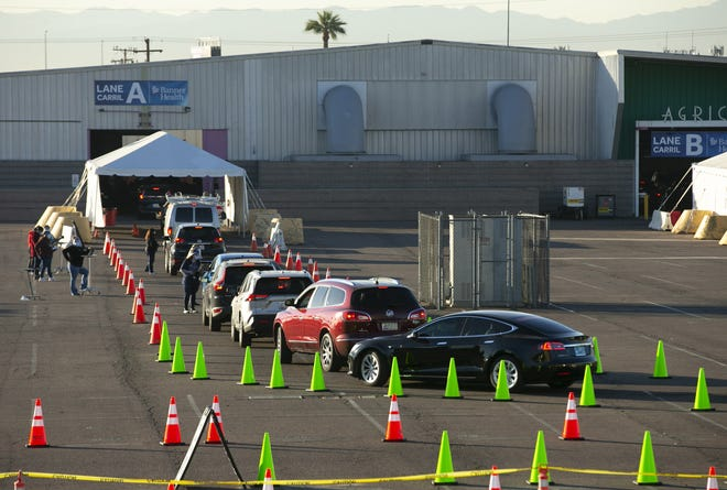 Drivers line up for the Pfizer-BioNTech COVID-19 vaccine at a vaccine site at the Arizona State Fairgrounds in Phoenix on Jan. 5.