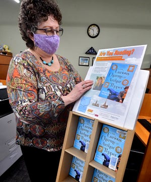"""Red Land Community Library manager Karen Hostetter attaches a poster to a display for the book """"The Curious Charms of Arthur Pepper,"""" by Phaedra Patrick, at the library Tuesday, Jan. 5, 2021.  The book is the selection for the """"One Book, One Community"""" program. Bill Kalina photo"""