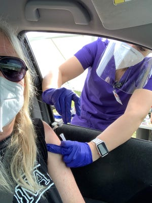 A Treasure Coast Community Health worker prepares to inoculate Cathy Woolsey with Moderna's COVID-19 vaccine Saturday, Jan. 2, 2021, at the Indian River County Fairgrounds in Vero Beach, Fla.