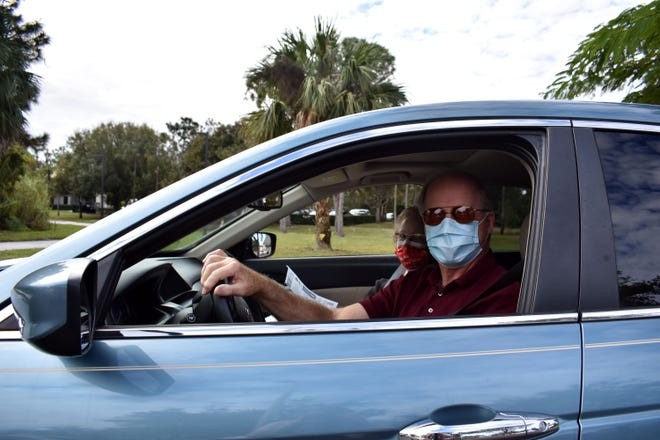 "Jon Gray, 74, and his wife Sharyn, 75, smile after receiving their first dose of the Moderna COVID-19 vaccine at a drive-thru clinic held Monday, Jan. 4, 2021, by the Florida Department of Health Martin County office in Stuart. ""It was very well organized,"" Jon said. ""I was surprised."""