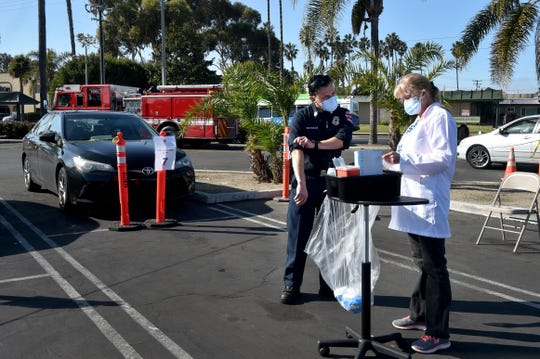 Oxnard Fire Capt.Uriel Estrada was screened by nurse Susan Landeros when he arrived for the Moderna COVID-19 vaccine during a driving clinic set up by Ventura County Public Health on Tuesday, Jan. 5, 2021.