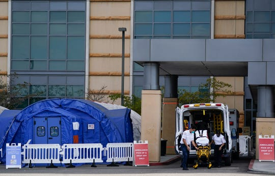 Medical workers remove a stretcher from an ambulance near medical tents outside the emergency room at UCI Medical Center, in Irvine, Calif., on Dec. 17, 2020.