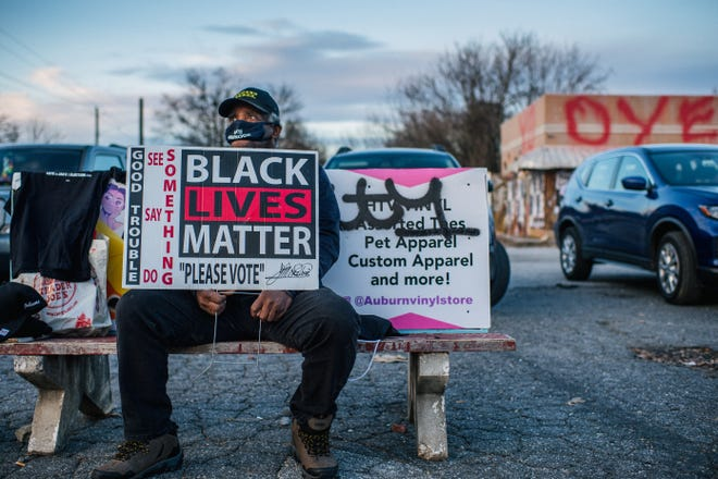 A Black Lives Matter supporter encourages people to vote Jan. 4 in Atlanta.
