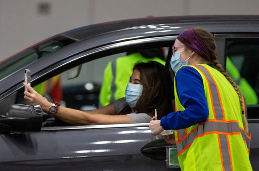 A woman takes a selfie with the medical worker who administered her COVID-19 vaccination at a drive-thru at Broadbent Arena in Louisville, Ky. on Jan. 4, 2021.