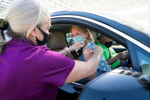 April Smith, RN, puts a bandage on Jeanne Biada, 66, after vaccinating her and her husband, Gregory Biada, 68, during a COVID-19 vaccine distribution run by the Collier Department of Health at North Collier Regional Park in Naples. Fla. on Jan. 4, 2021.