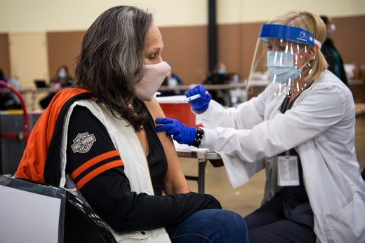 Kellie Grover, left, receives her first dose of the Moderna COVID-19 vaccine through the Knox County Health Department at the Knoxville Expo Center on Monday, January 4, 2021.