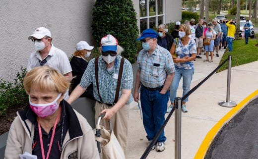 Seniors stand in line to make an appointment to receive the Moderna COVID-19 vaccine outside the King's Point clubhouse in Delray Beach, Fla. on Dec. 30, 2020.