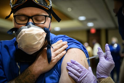 Nurse Chris Nelson gets the COVID-19 vaccine at Cape Fear Valley Medical Center on Tuesday, Dec. 15, 2020.