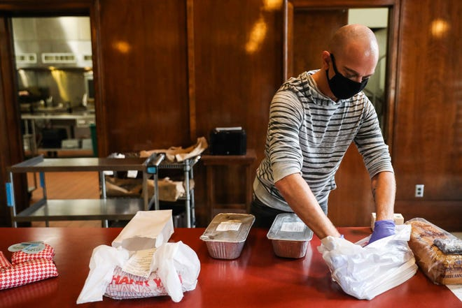 Curbside was the name of the game in 2020. At Austin's Cafe Divine, a community restaurant housed inside St. David's Episcopal Church downtown, Kenneth Spivey prepares a curbside order in July.