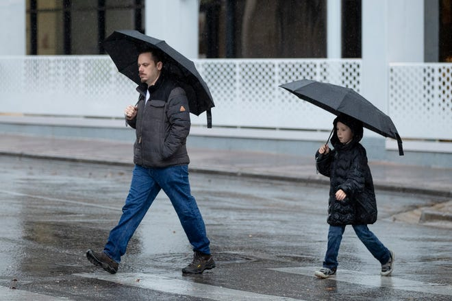 Brendan Walsh and his 8-year-old son, Riley, walk along Congress Avenue in the rain Jan. 6. The wet weather will return this week, and this time it will stick around through at least Sunday.