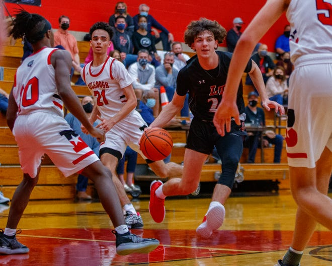 Lake Travis guard Aaron Jacob drives the ball to the basket against the Bowie Bulldogs during the third period at the District 26-6A boys basketball game Jan. 5 at Bowie High School. Lake Travis pulled away for a 64-51 win to remain unbeaten in district play.