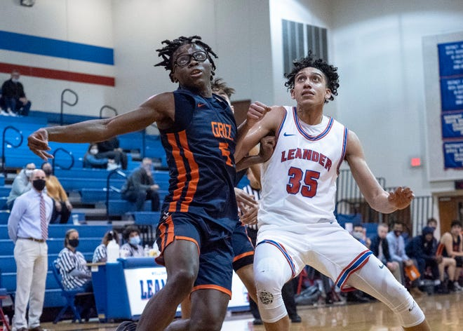 Glenn's Jaylen Thompson, left, and Leander's Noah Robledo jostle for position for a rebound during the second half of a District 25-5A basketball game Tuesday at Leander High School. Thompson helped Glenn defeated Leander 55-52 in a crucial district win.