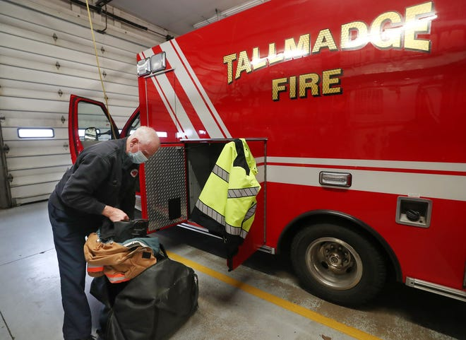 Tallmadge firefighter and medic David Lee loads his turnout gear into the med unit as he starts his shift at Tallmadge Fire Station 1 on Wednesday, Jan. 6, 2021 in Tallmadge.  [Mike Cardew/Beacon Journal]