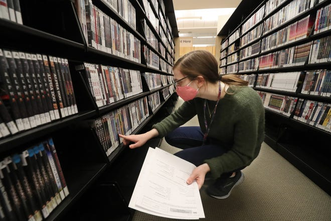 Student assistant Grace Benson looks for a DVD as she fills a request Wednesday in the culture and audiovisual division at Akron-Summit County Public Library in downtown Akron.