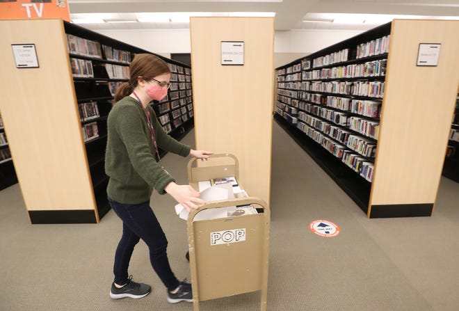 Grace Benson, a student assistant at Akron-Summit County Public Library, pushes a cart through the stacks Wednesday in downtown Akron.